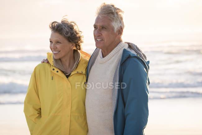 Felice coppia anziana in piedi sulla spiaggia al tramonto — Foto stock