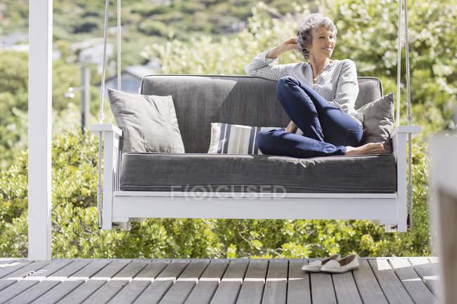 Glücklich ältere Frau sitzt auf Schaukel in Veranda — Stockfoto