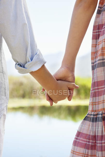 Close-up of kids holding hands at lake in nature — Stock Photo