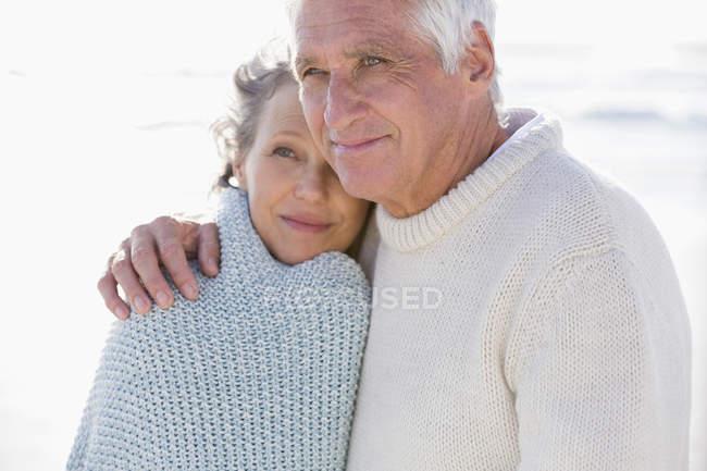Крупный план вдумчивой пожилой пары, обнимающейся на пляже — стоковое фото