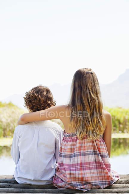 Blick von hinten auf Geschwister, die zusammen am Holzsteg am See in der Natur sitzen — Stockfoto