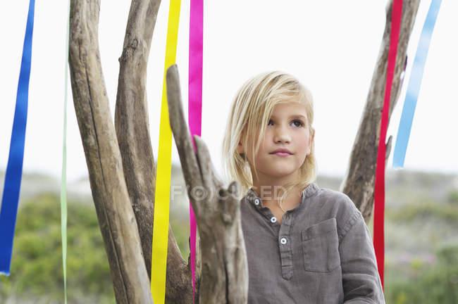 Menina loira pensativa em pé perto da árvore decorada com fitas — Fotografia de Stock