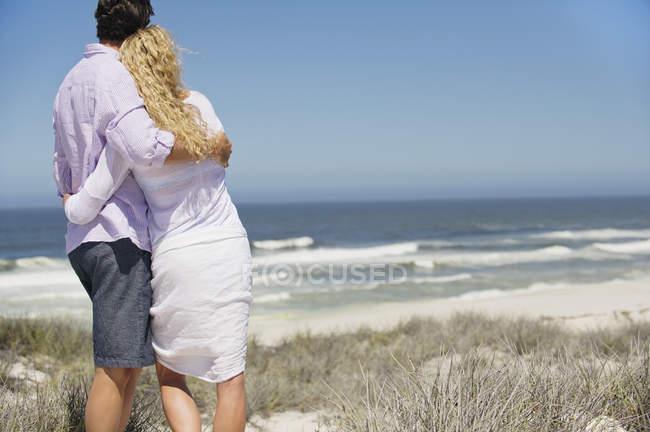 Задній вид романтична пара embracing і, дивлячись на вид на пляж — стокове фото