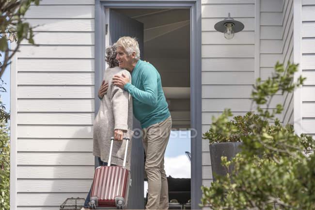 Hombre mayor acogedora mujer en la puerta - foto de stock