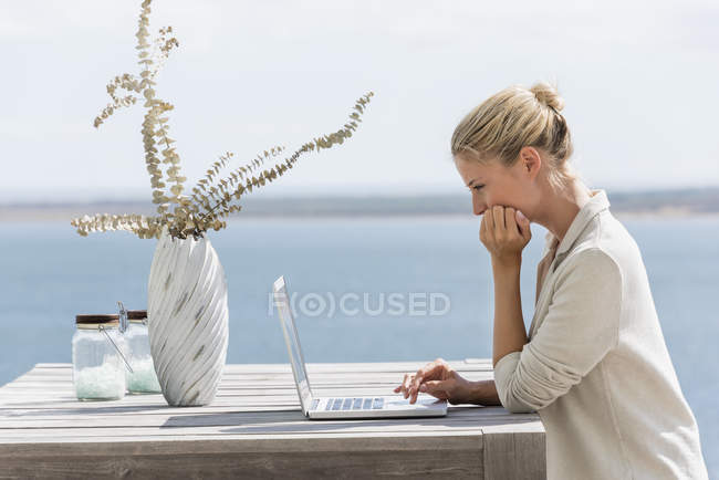 Focused young woman using a laptop at wooden table in nature — Stock Photo