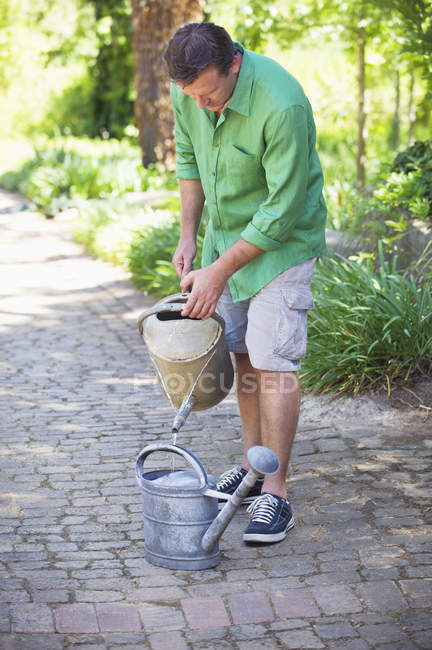 Man filling water into watering can in garden — Stock Photo