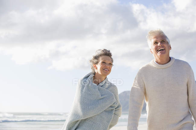 Happy senior couple walking on beach under cloudy sky — Stock Photo