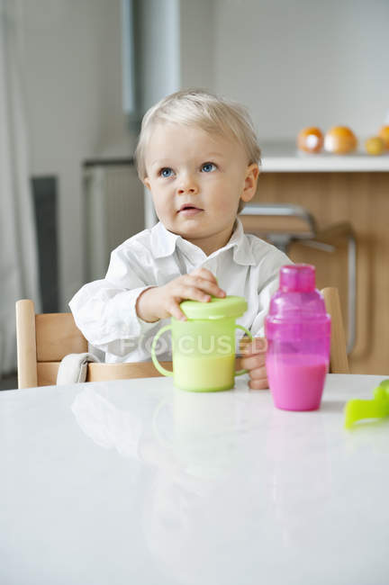 Cute baby boy sitting at dining table in kitchen — Stock Photo