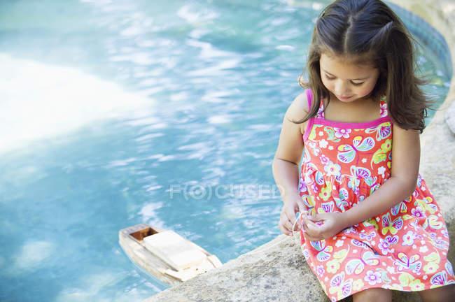 Kleines Mädchen sitzt am Rand des Swimmingpools und spielt mit Spielzeugboot im Wasser — Stockfoto