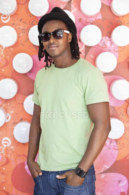 Sorrindo homem usando óculos de sol e de pé no café — Fotografia de Stock