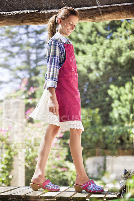 Улыбающаяся девушка в фартуке ходит по пирсу в солнечном саду — стоковое фото