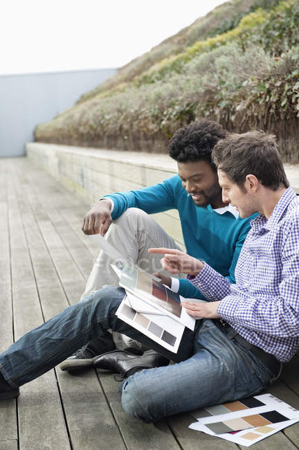 Male friends choosing color swatches on boardwalk in nature — Stock Photo