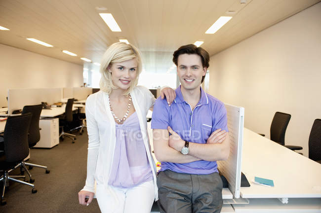 Portrait de couple d'affaires souriant appuyé sur le bureau au bureau — Photo de stock
