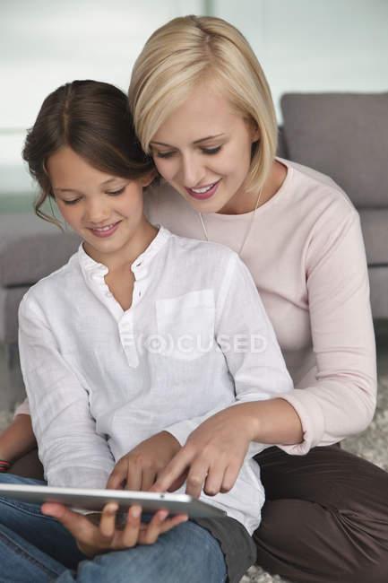 Woman assisting daughter in using digital tablet — Stock Photo