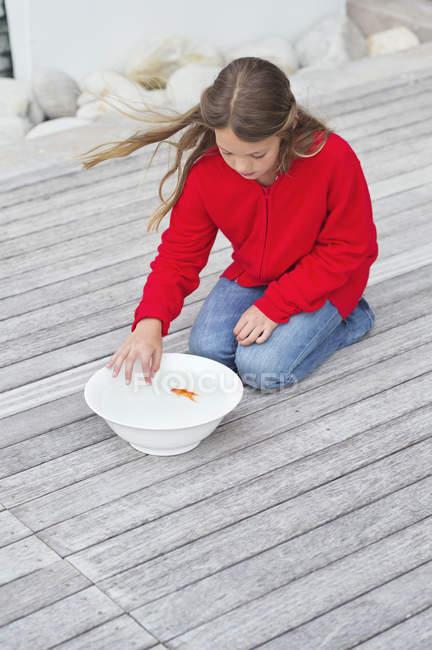 Ragazza toccando pesce rosso in ciotola sul molo di legno — Foto stock
