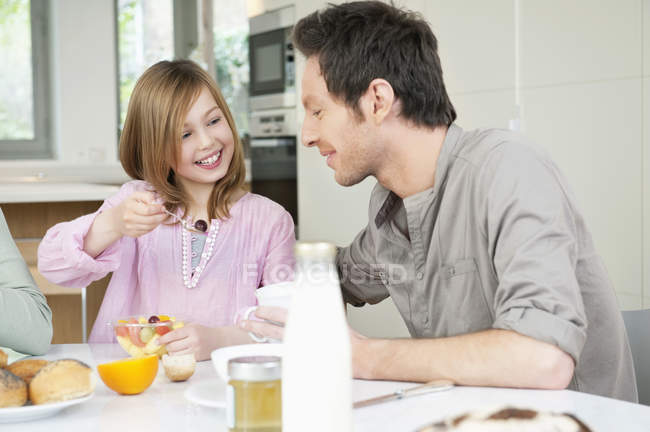 Man eating breakfast with daughter in kitchen — Stock Photo