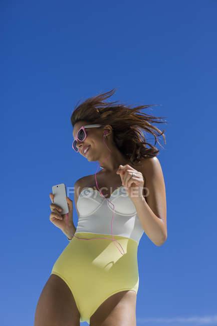 Счастливая женщина в купальнике слушает музыку с мобильного телефона перед голубым небом — стоковое фото