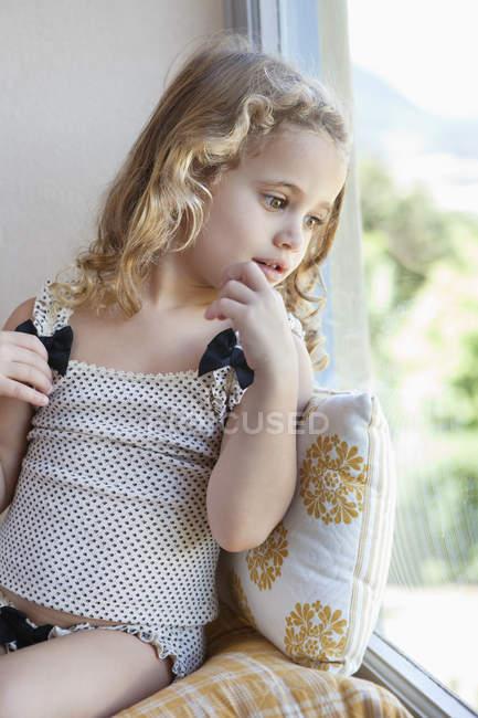 Милая маленькая девочка смотрит из окна на дом — стоковое фото