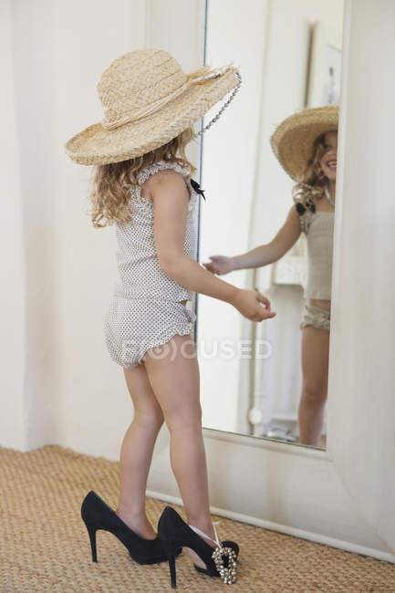 Petite fille mignonne portant mère accessoires surdimensionnés et regardant miroir — Photo de stock