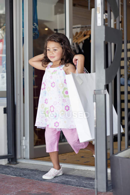 Cute little girl walking out of shopping mall with shopping bags — Stock Photo