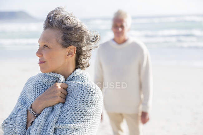 Close-up of thoughtful senior woman standing on beach with husband on background — Stock Photo