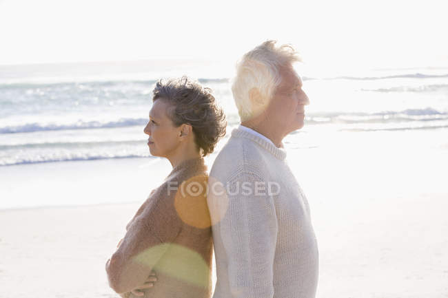 Thoughtful senior couple standing back to back sunny on beach — Stock Photo
