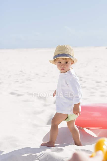 Крупный план милого мальчика в соломенной шляпе, стоящего на пляже — стоковое фото