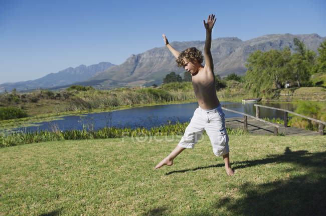 Cute little boy doing cartwheel against on grass in nature against mountains — Stockfoto