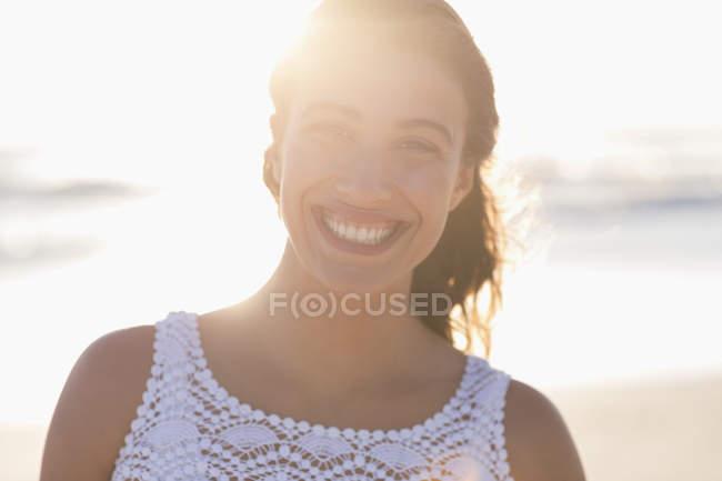 Портрет усміхнений молоду жінку на сонячному пляжі — стокове фото