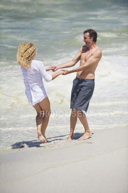 Coppie allegre scherzare sulla spiaggia sabbiosa — Foto stock