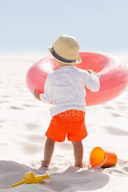 Вид сзади на мальчика, играющего с надувным кольцом на пляже — стоковое фото