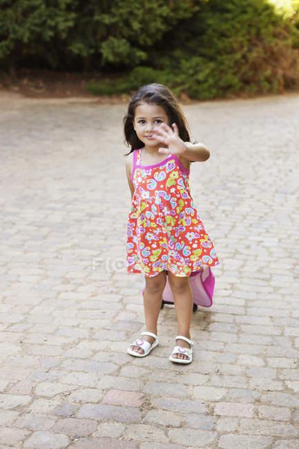 Menina no verão vestido carregando bagagem e a mão que te acenava ao ar livre — Fotografia de Stock