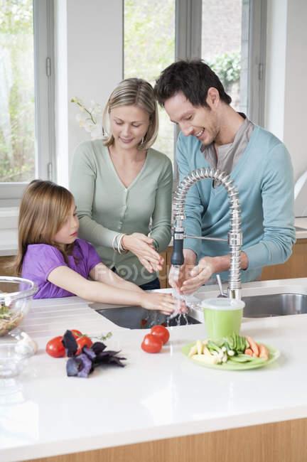 Happy family preparing food in kitchen — Stock Photo