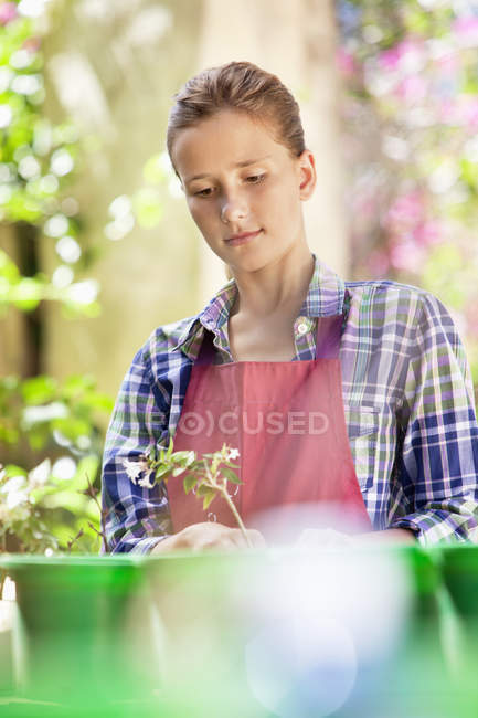 Thoughtful girl in apron gardening outdoors — Stock Photo