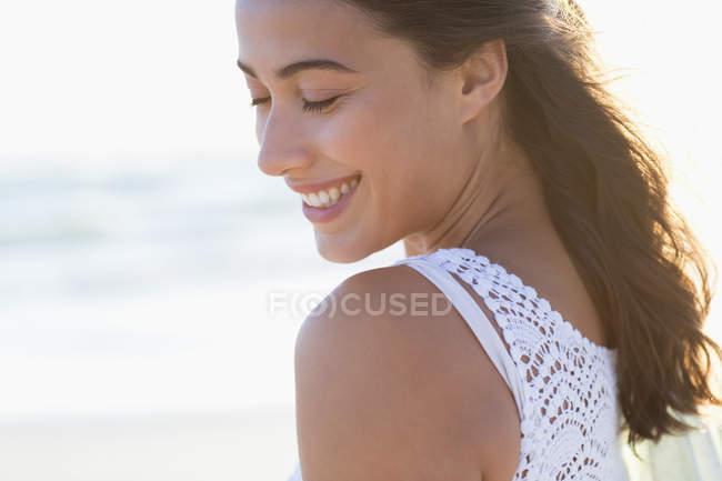 Giovane donna sorridente con gli occhi chiusi sulla spiaggia alla luce del sole — Foto stock