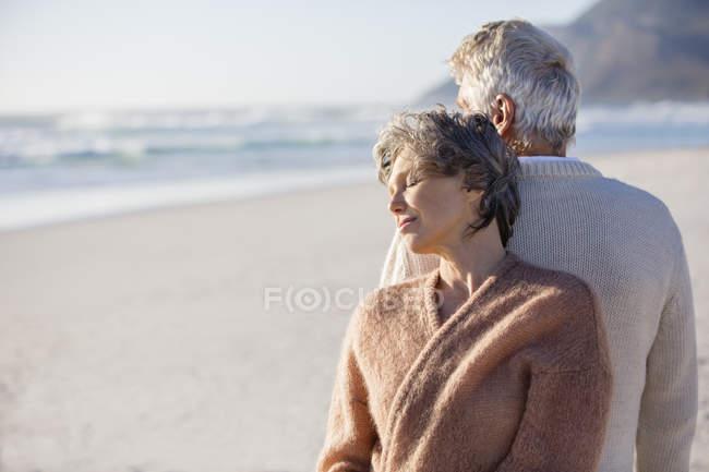 Nahaufnahme eines entspannten, nachdenklichen Senioren-Paares, das Rücken an Rücken am Strand steht — Stockfoto
