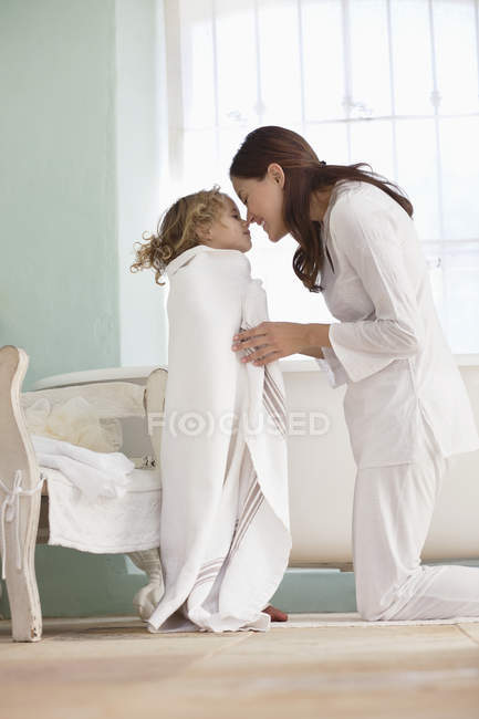 Woman rubbing noses with daughter wrapped in towel after bath — Stock Photo