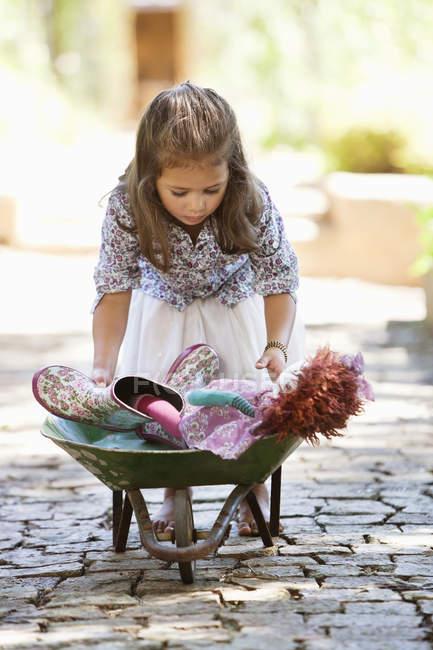 Мила маленька дівчинка на відкритому повітрі натисканням Тачка з іграшками — стокове фото