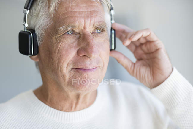 Senior man listening to music with headphones and looking away — Stock Photo