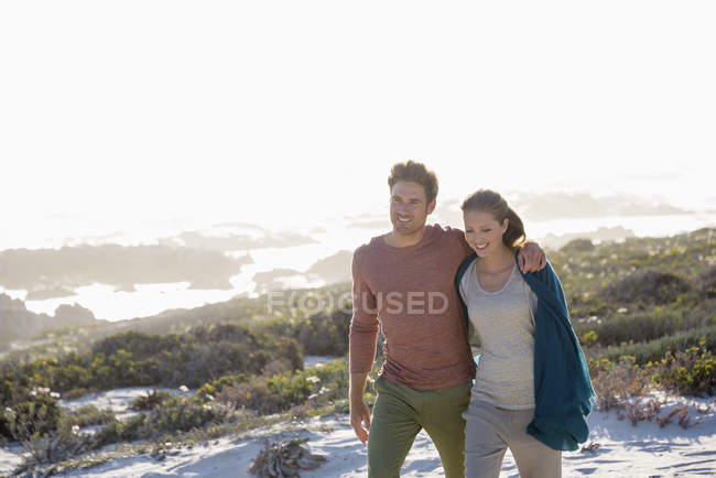 Relaxed romantic couple walking on coast together — Stock Photo