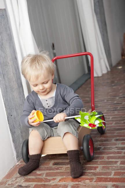 Веселый маленький мальчик играет с вертушкой на тележке — стоковое фото