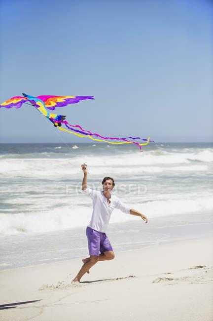 Man having fun with flying kite on beach — Stock Photo