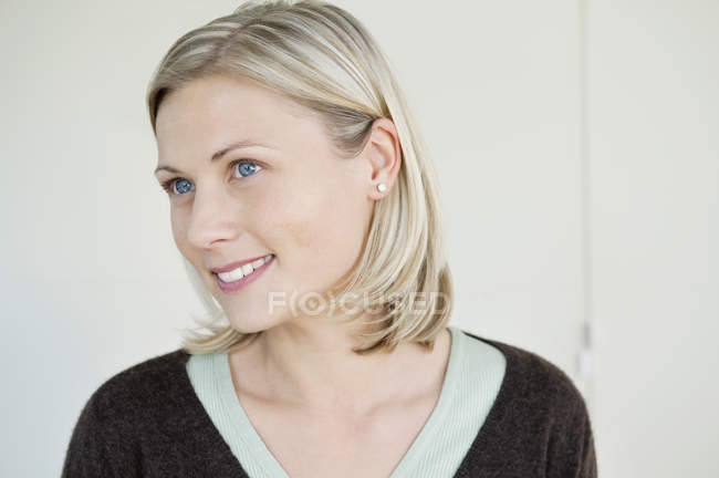 Close-up of blond woman with blue eyes smiling and looking away — Stock Photo