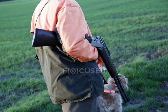 Мисливець з рушницею, що відпочиває після полювання, вибірковий фокус. — стокове фото
