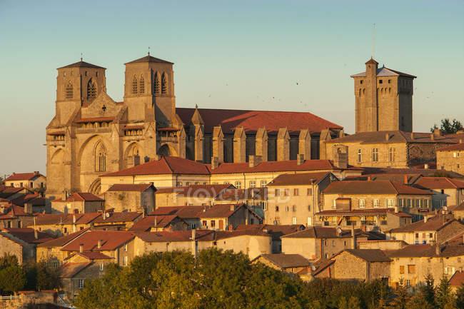 France, Auvergne-Rhônes-Alpes, Haute-Loire, La Chaise-Dieu, vue sur l'église abbatiale Saint Robert et la ville médiévale au coucher du soleil — Photo de stock