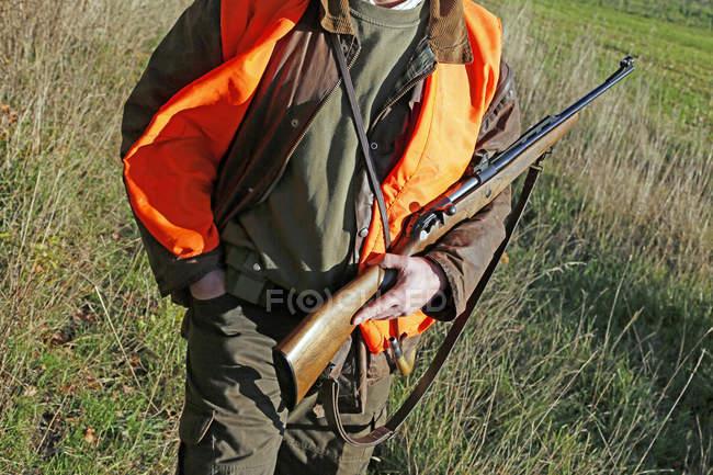 Мисливець тримає рушницю в руках, селективний фокус — стокове фото