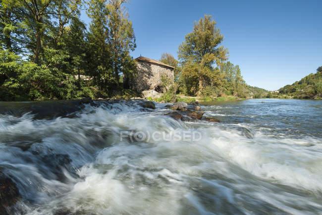 Francia, Auvernia-Ródanos-Alpes, Haute-Loire, salpicadura del río Loira en las montañas y el antiguo edificio - foto de stock