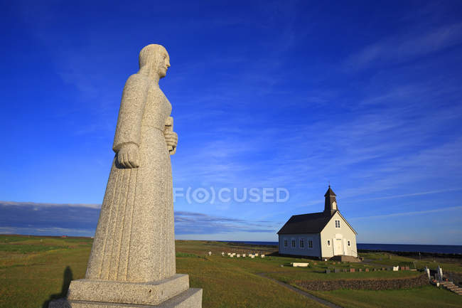 Iceland, Sudurland. Strandarkirkja, Selvogur. Small church and statue on field - foto de stock
