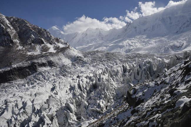 Пакистан, район Гилар-Балтистан, Нагар-ван, Минапин, вид над Минапинским хребтом и высокими заснеженными горами хребта Ракихи — стоковое фото