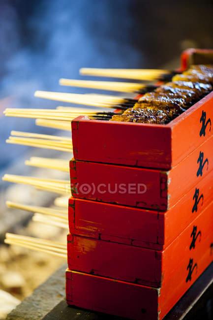 Tofu frit sur bâtons de bambou empilés dans des boîtes rouges, Iga ueno, Japon — Photo de stock